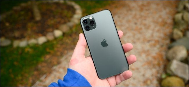 A man's hand holding an Apple iPhone 11 Pro.