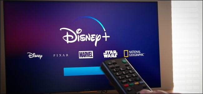 A remote control pointing at a TV with Disney+ on it.