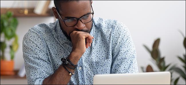 Un hombre tapándose la boca con la mano y mirando la pantalla de un portátil.