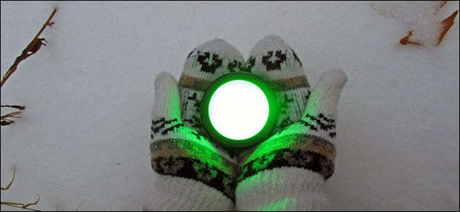 A pair of gloved hands holding an Echo button glowing green over the snow.