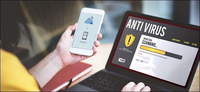 A hand holding a smartphone that's running an antivirus, next to a laptop on a desk that's also running an antivirus scan.