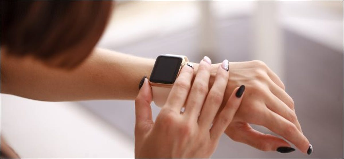 A woman pressing the side button on an Apple Watch she's wearing.