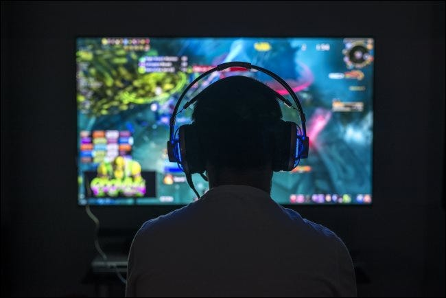 A young gamer playing a PC game while wearing headphones.