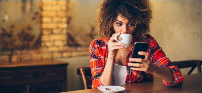 A woman seated at a table looking at a smartphone and drinking coffee.