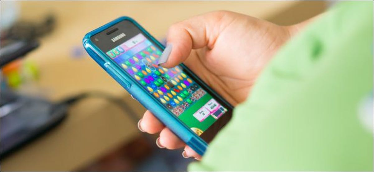 A person playing Candy Crush Saga on a Samsung Android smartphone.