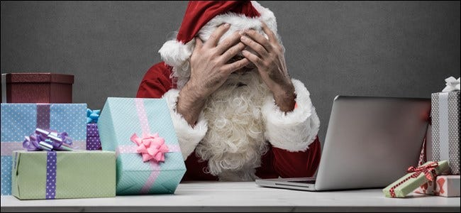 Santa sitting in front of his laptop and a stack of gifts, covering his face with his hands.