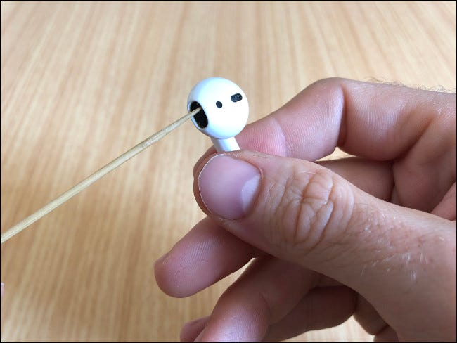 A man's hand holding an AirPod and cleaning the speaker with Toothpick.