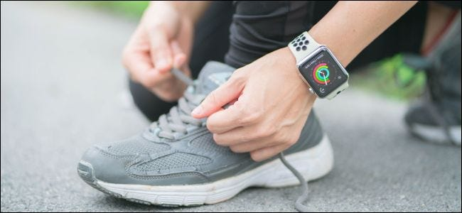 A person tying shoelaces and wearing an Apple Watch.