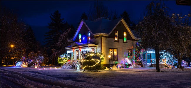 Snow-covered private home with bright Christmas lights and decorations