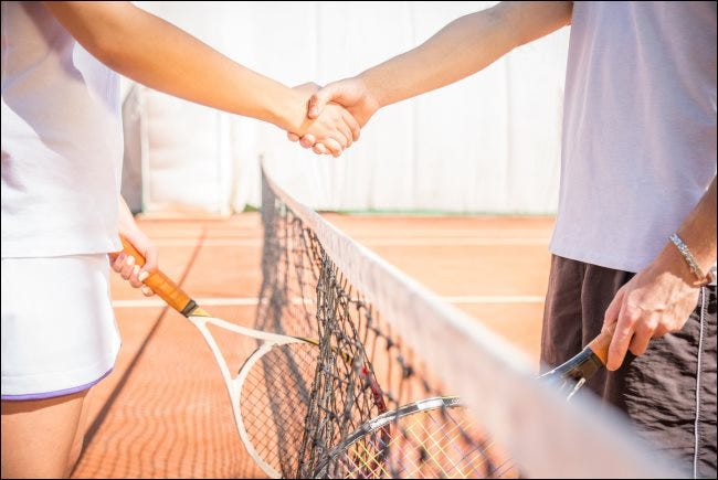 Two players shaking hands at a tennis court
