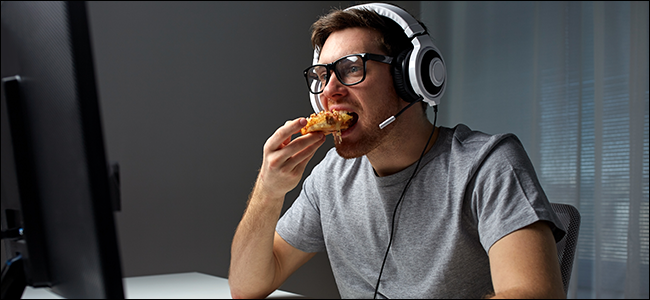 A man sitting in front of a computer, wearing a headset, and eating pizza.