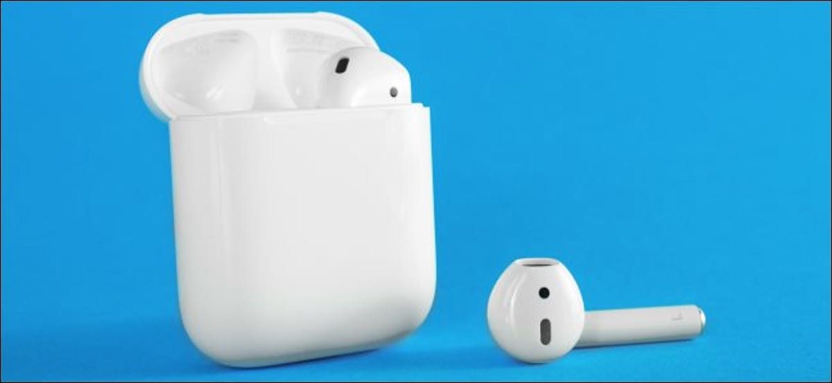 One Apple AirPod in the charging case and the other lying beside it.