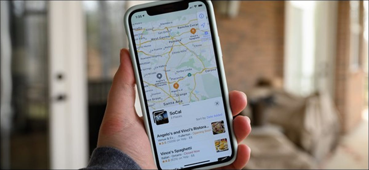 A hand holding an iPhone with an Apple Maps Collection onscreen.