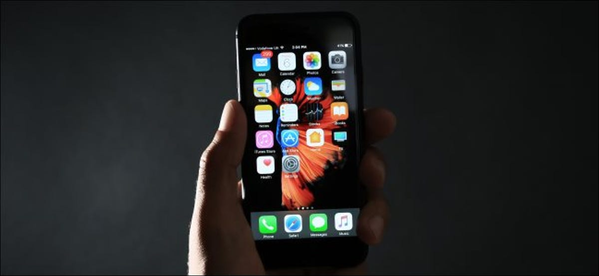 A hand holding a black iPhone in the dark.