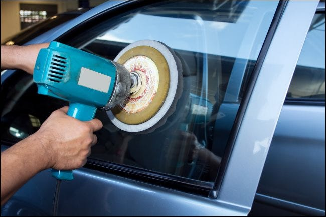 A man's hands polishing a car window with a power buffer machine.