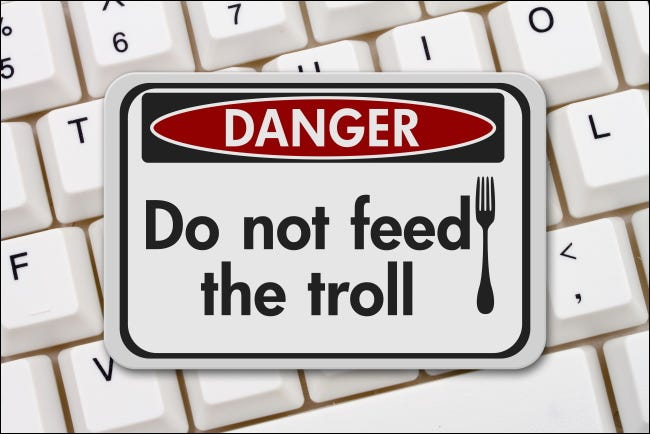 """A """"Danger: Do not feed the troll"""" sign on a computer keyboard."""