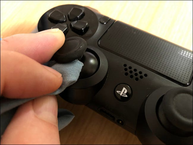 A hand cleaning an analog stick with a cloth on a DualShock 4 Controller.