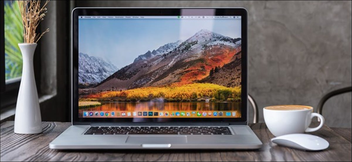 A MacBook Pro open on a table next to a mug and a vase of flowers.