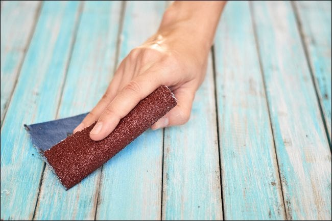 A hand sanding wood with a piece of sandpaper.