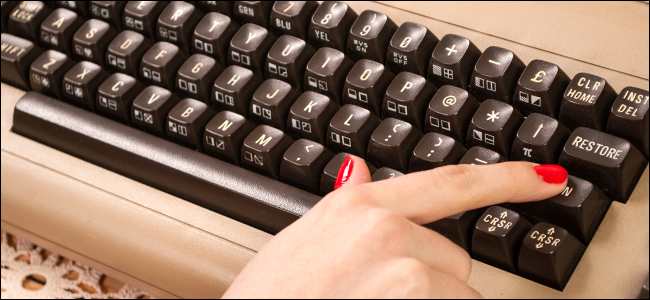 A woman typing on an old keyboard.