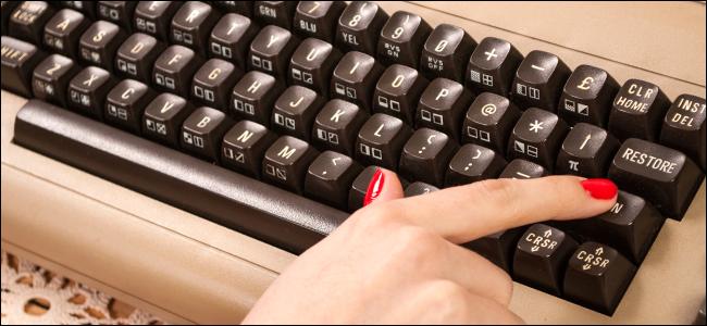 Una mujer escribiendo en un teclado antiguo.