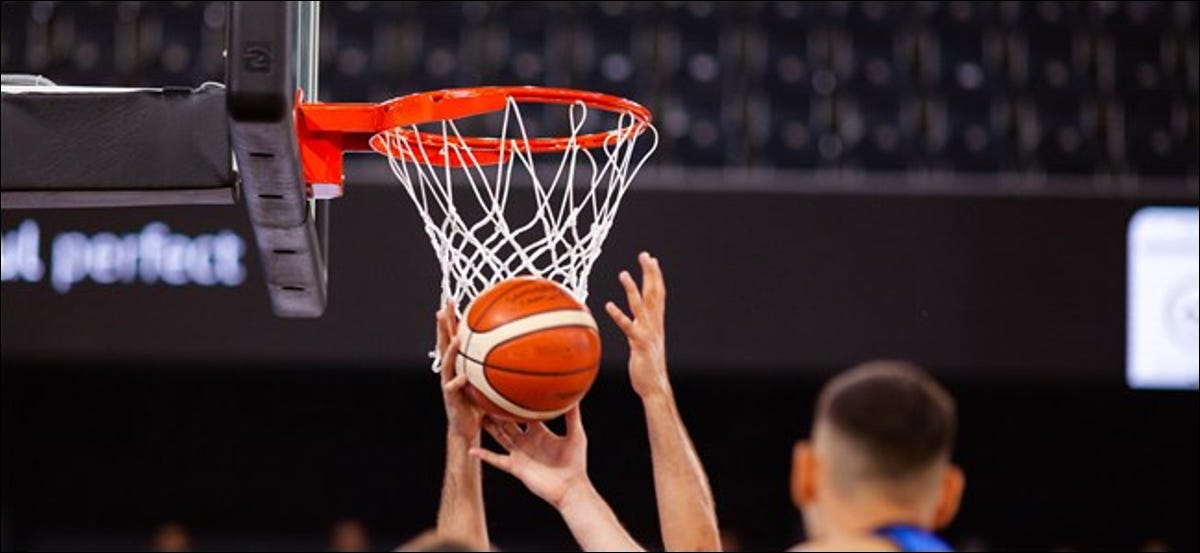 Hands reaching for a basketball in front of the net.