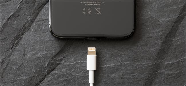 A Lightning cable about to be plugged into an iPhone X.