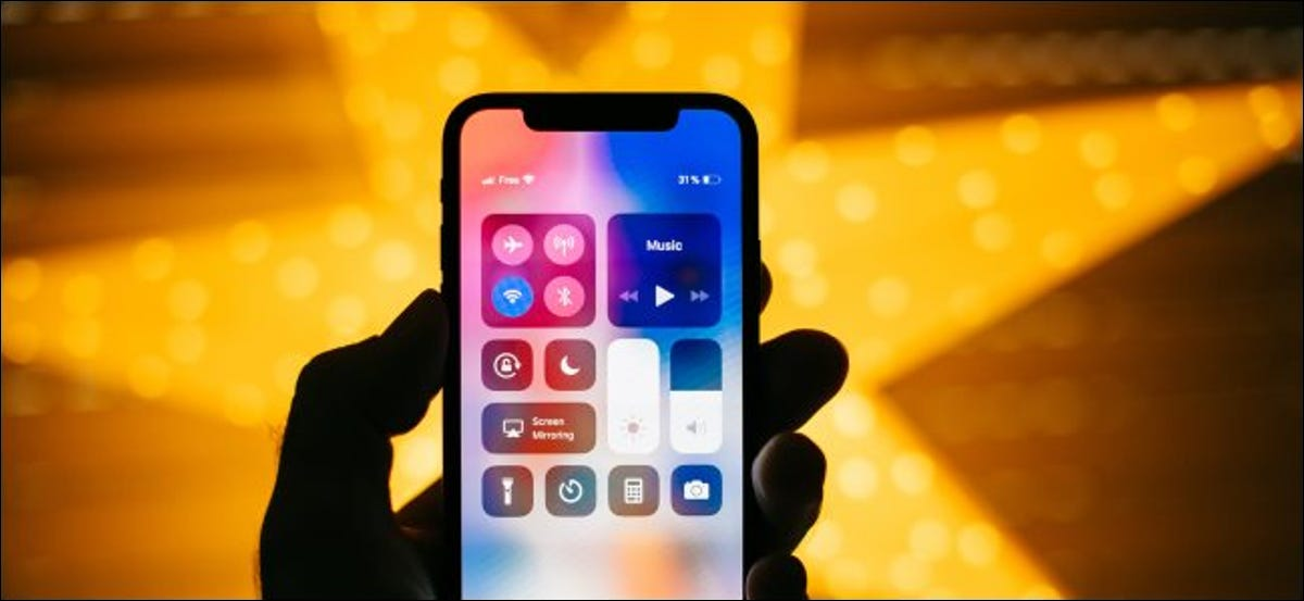 A hand holding an iPhone X with the Control Center open.