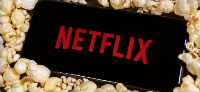 The Netflix logo on a smartphone sitting on a pile of popcorn.