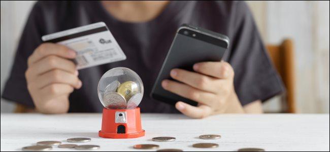 Las manos de un niño sosteniendo una tarjeta de crédito y un teléfono inteligente, y un juego de gacha en la mesa.