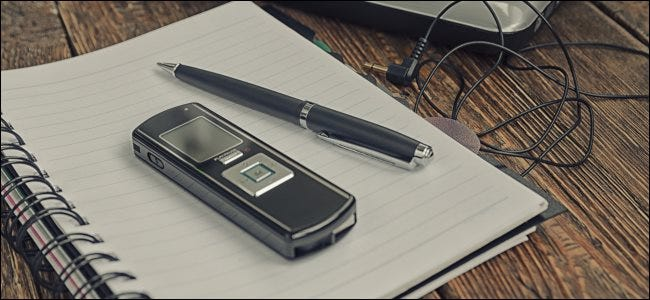 A digital voice recorder and pen sitting on top of a notepad.