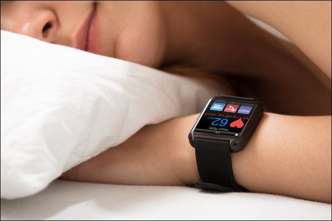 A woman sleeping while a smartwatch shows her heartbeat.