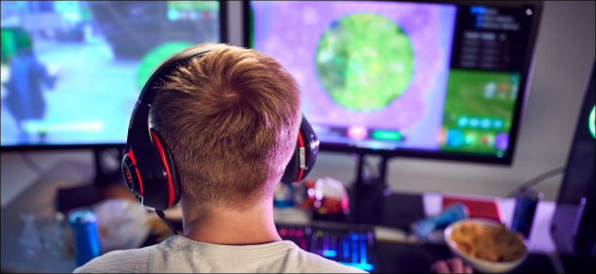 The back of a young boy, who's wearing headphones and sitting at a computer with dual monitors.