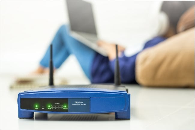 A wireless router with a child using a laptop in the background.