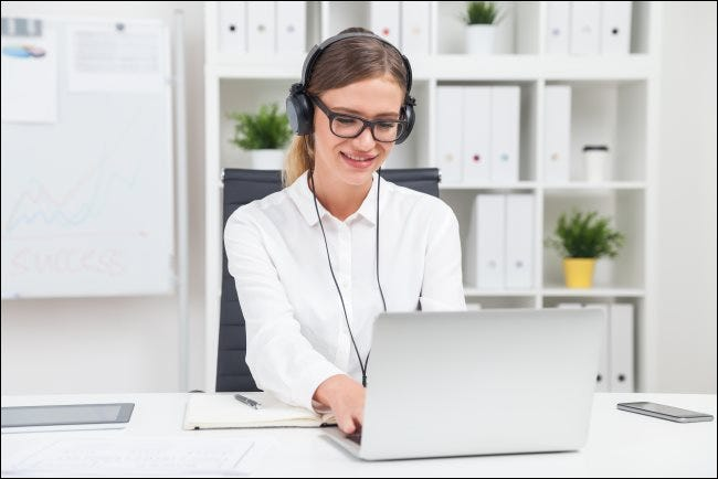 A woman wearing headphones and typing on a laptop.