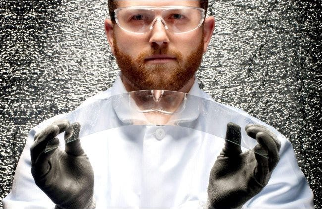 A scientist holding a piece of bendable Corning glass.