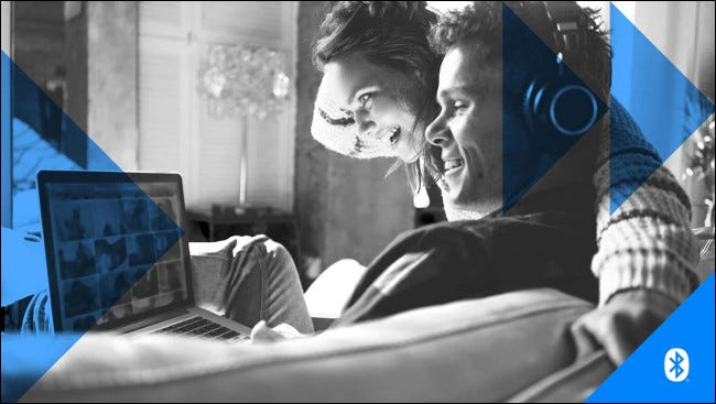 A man and woman wearing headphones while looking at a laptop computer screen.