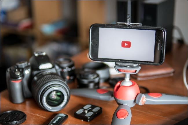 A camera sitting on a table next to a smartphone that's mounted on a table tripod.