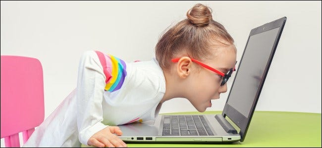 Kid in Glasses Leaning Into Laptop