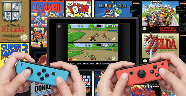 "Two sets of hands holding Nintendo Switches playing ""Mario Kart"" with other Nintendo NES games behind the screen."