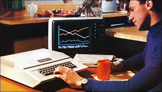 Un hombre en un escritorio escribiendo en el gran teclado Apple II en un anuncio de 1977.