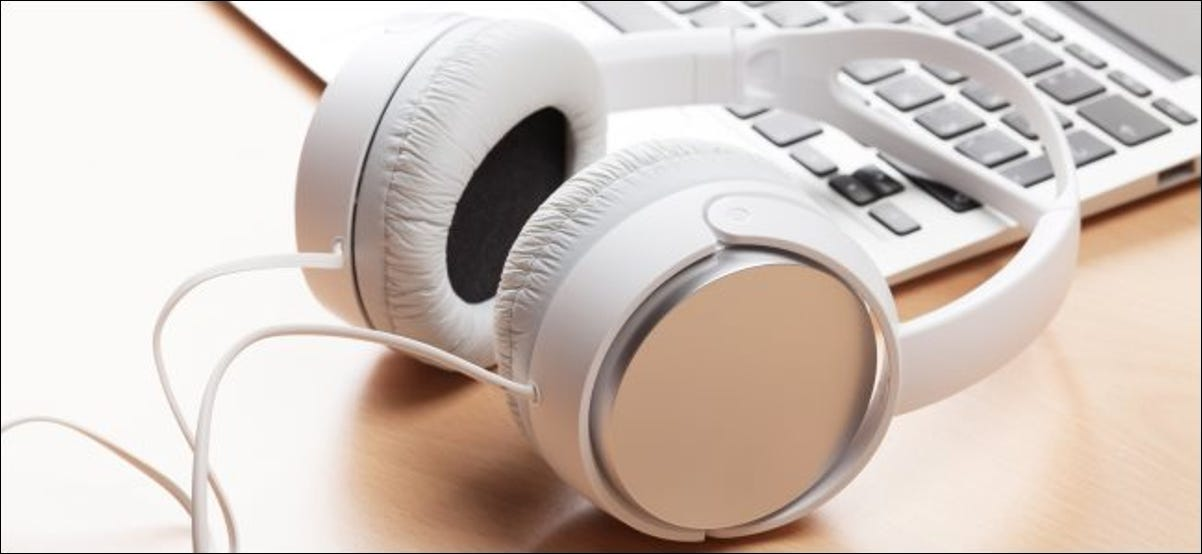 A pair of clean white headphones sitting near a laptop on a table.