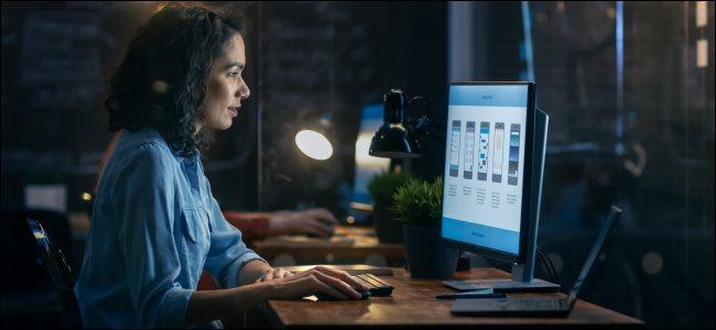 Una mujer que trabaja en una computadora de escritorio, con una computadora portátil abierta al lado.