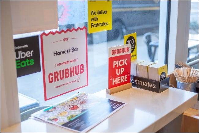 Signs for GrubHub, Postmates, and Uber Eats in a restaurant.