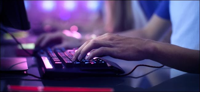 Hands on a PC gamer keyboard illuminated in purple light.