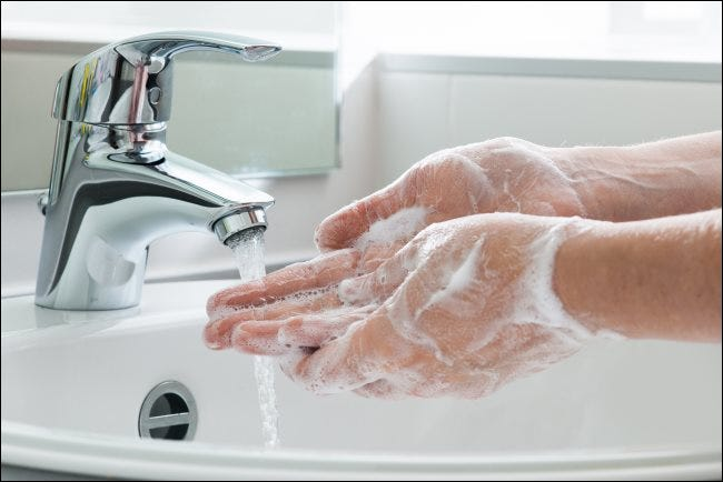 Washing hands with soap under a water tap.