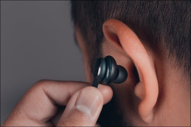 A man inserting an earbud into his ear.