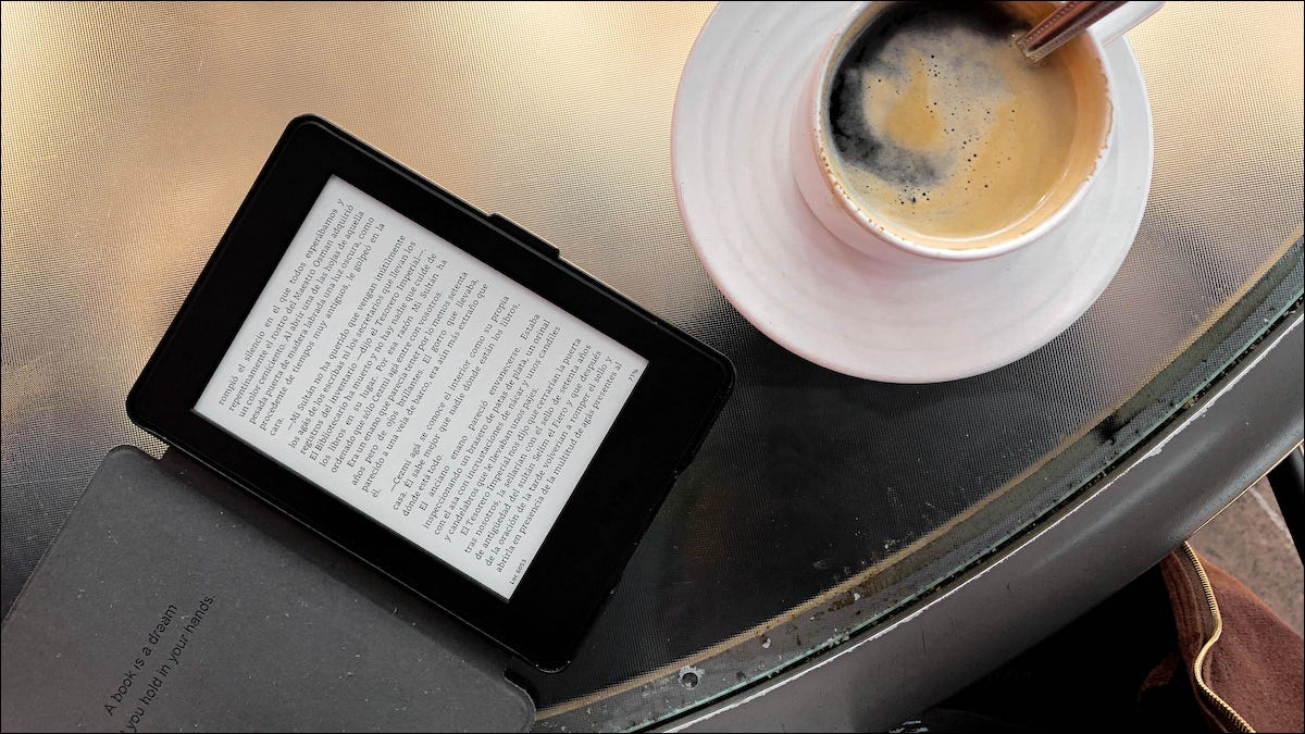 Kindle laying on a tablet next to a cup of coffee