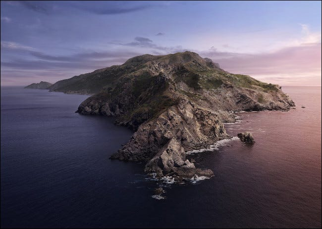 The macOS Catalina basic wallpaper of a rock island surrounded by the sea.