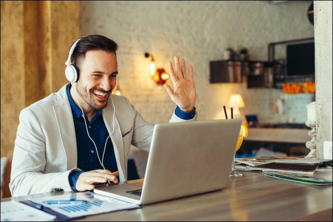 A man wearing headphones and waving at his laptop.